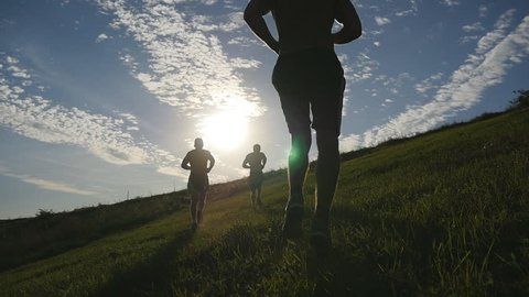 Young men running over green hill over blue sky background. Male athletes is jogging in nature at sunset. Sport runners jogging uphill outdoor at sunrise with flare. Cross-country training. Slowmotion
