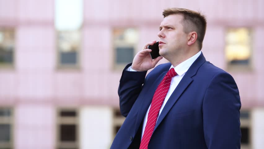 A man in a suit with red tie talking on the phone on the street | Shutterstock HD Video #19859614