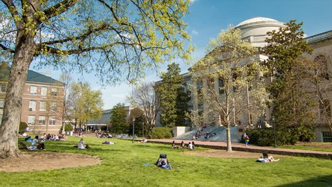 RALEIGH / DURHAM, NC - 2016: Wilson Library at University of North Carolina Chapel Hill Building Exterior with Students Sitting on Grass Lawn of Polk Place Park