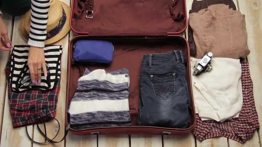 woman's hands packing a suitcase