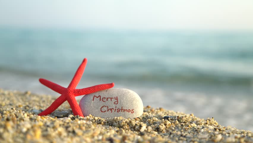 4k0014close up of red starfish leaning on a small rock on a beach with merry christmas written on the rock - Merry Christmas Beach Images
