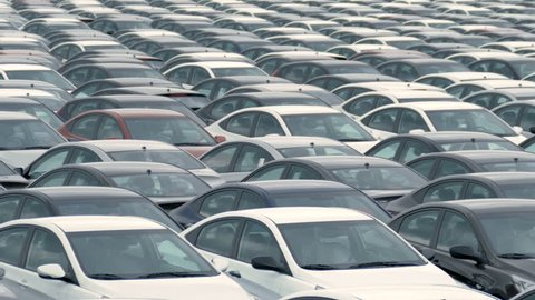 a large number of cars in the Parking lot. Storage area for new unsold cars at the plant