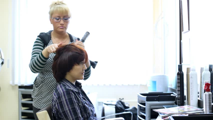Hairdresser does hairdo by hair dryer for woman in salon
