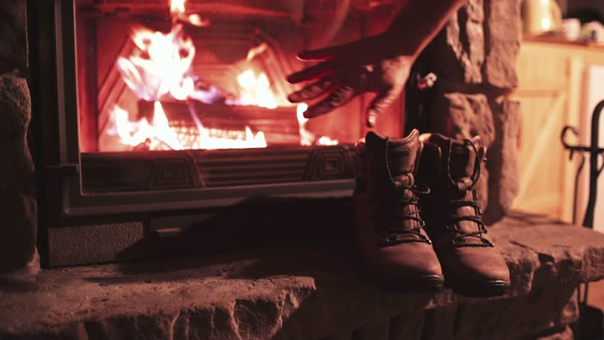 Man Hand puts Winter Boots on a Shelf near Fireplace to get Warm. 4K. Vintage folk boots near the Cozy Fireside. Shoes getting dry near the burning fire at home, in chalet. Autumn and Winter Concept | Shutterstock HD Video #19972903