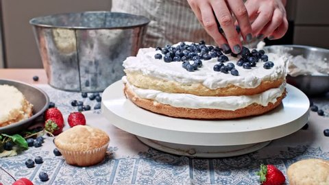 Girl makes cake, putting blueberry on shortcake, sequence of close ups