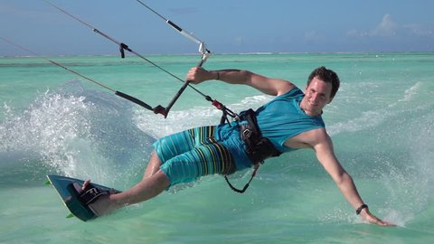 SLOW MOTION: Happy smiling kite surfer kiteboarding in turquoise ocean on sunny day. Cheerful kiteboarder kiting and splashing sea water in blue lagoon of tropical island Zanzibar on summer vacation