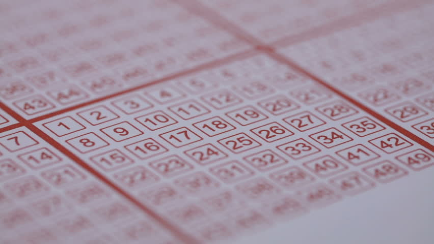 Close-up Of Person's Hand Marking Number On Lottery Ticket With Pencil