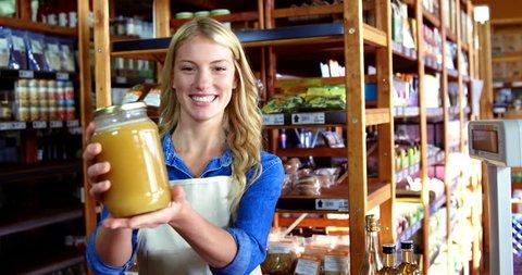 Portrait of smiling Caucasian female staff holding jar of honey in supermarket 4k