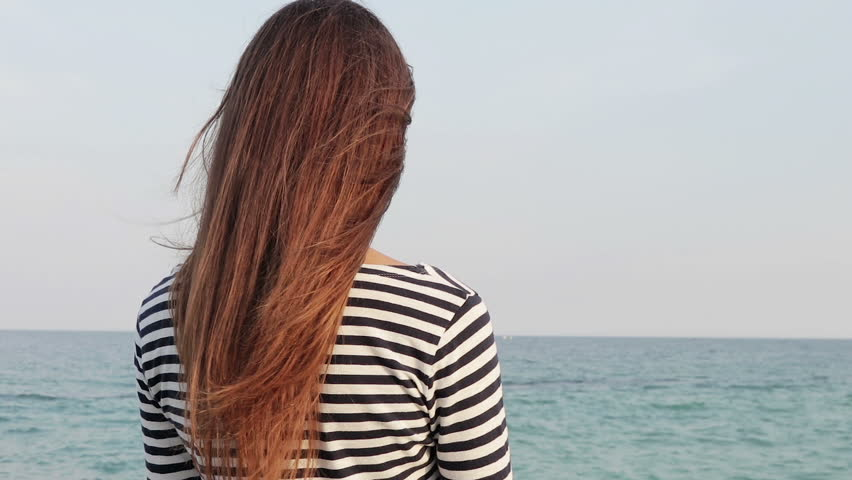 Young woman with long hair in a striped shirt looking at the sea, view from the back, slow motion | Shutterstock HD Video #20050717