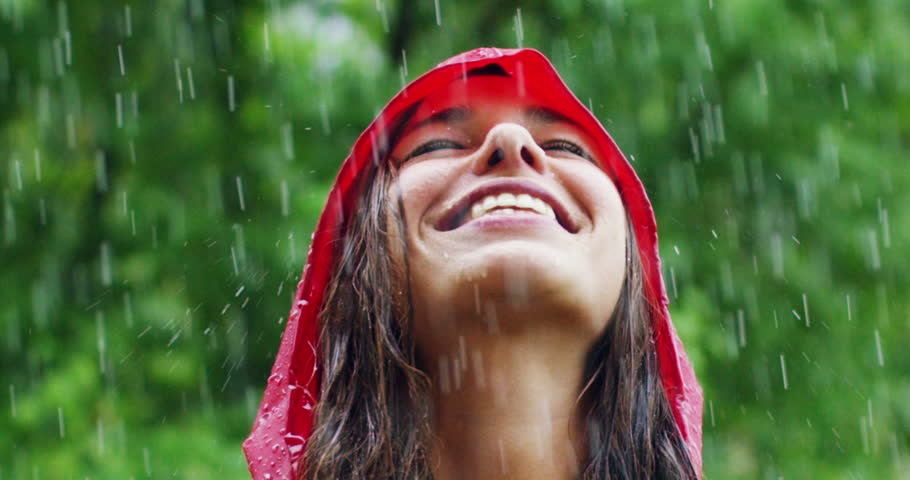 A happy woman smiles in the rain, the woman immersed in the nature of dance under the happy and free rain in slow motion. Concept of love, nature, happiness, freedom.
