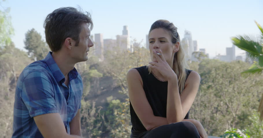 Non-smoking young man walks away after girlfriend smokes cigarette and quickly replaced by a young man with cigarettes in urban park with LA skyline. Medium shot, recorded hand-held in real time.