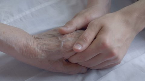 Close-up of a young man holding his grandparent's hand. Caring and loving a sick senior.
