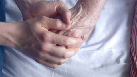 Close-up of holding an elderly patient's hand at the hospital. Young man caring his grandmother's health.
