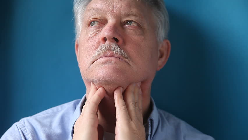 a mature man feels the lymph glands in his neck