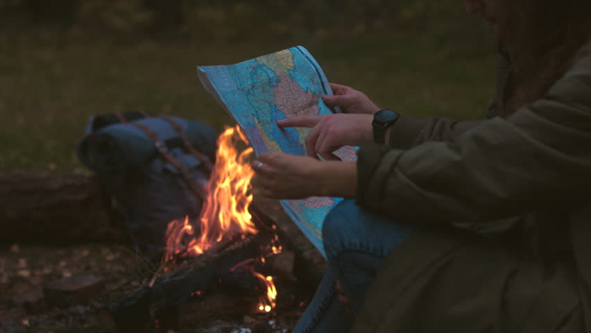 CINEMAGRAPH - Hikers couple studying the map near bonfire. Motion photo seamless loop. 4K UHD RAW edited footage