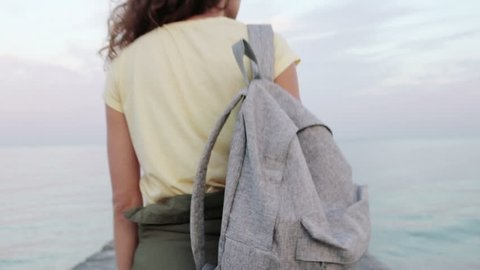 Young curly brunette in a yellow T-shirt with a backpack walking along the pier, stops at the edge and looks at the sea, view from the back, slow motion