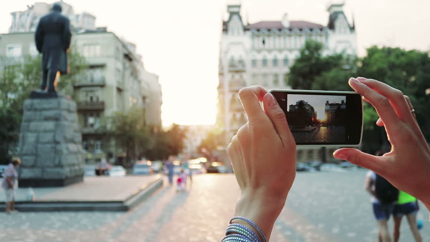 Female hand photographed on a smart phone historic downtown during sunset.  Tourist making a photo by mobile phone. Slow motion. | Shutterstock HD Video #20180524