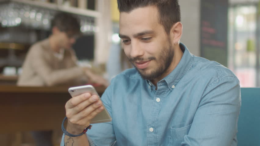Hispanic Ethnicity Young Man using Mobile Phone at Cozy Coffee Shop. Shot on RED Cinema Camera in 4K (UHD). | Shutterstock HD Video #20201725