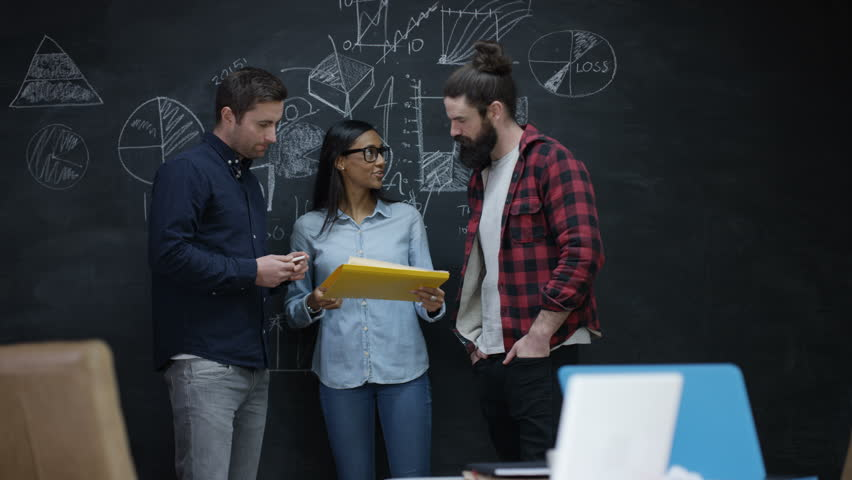 4K Young professional team in startup company discussing business plan & working together. Chalkboard background with charts, graphs & symbols. Shot on RED Epic. | Shutterstock HD Video #20208514