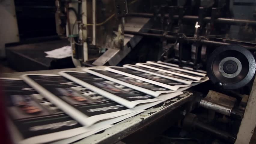 Newspaper being printed in printing press