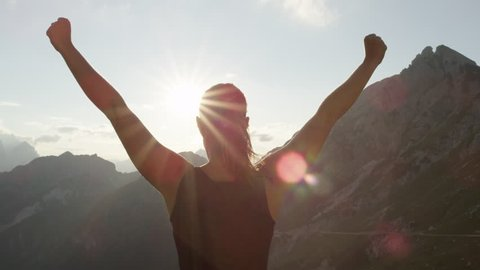 SLOW MOTION, CLOSE UP: Young female standing on the edge of the cliff and raising her hands up against high rocky mountains sunbathing in evening sun. Happy girl enjoying success and stunning view