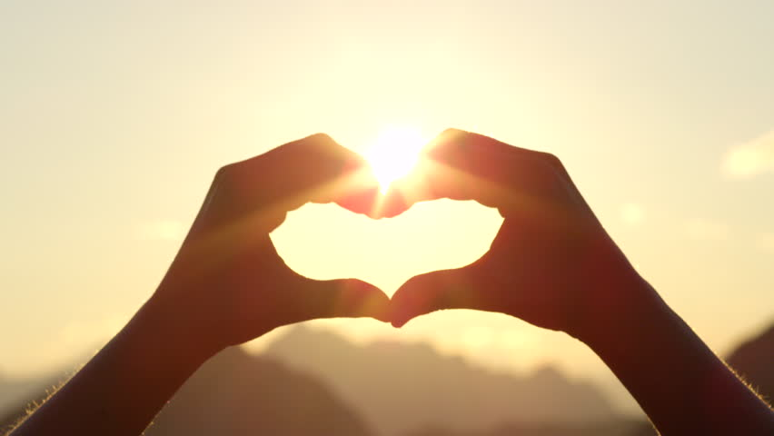 SLOW MOTION, CLOSE UP: Unrecognizable woman catching setting sun with her heart shaped fingers. Young girl making the symbol of love with her hands against stunning golden sky and rising morning sun | Shutterstock HD Video #20240854