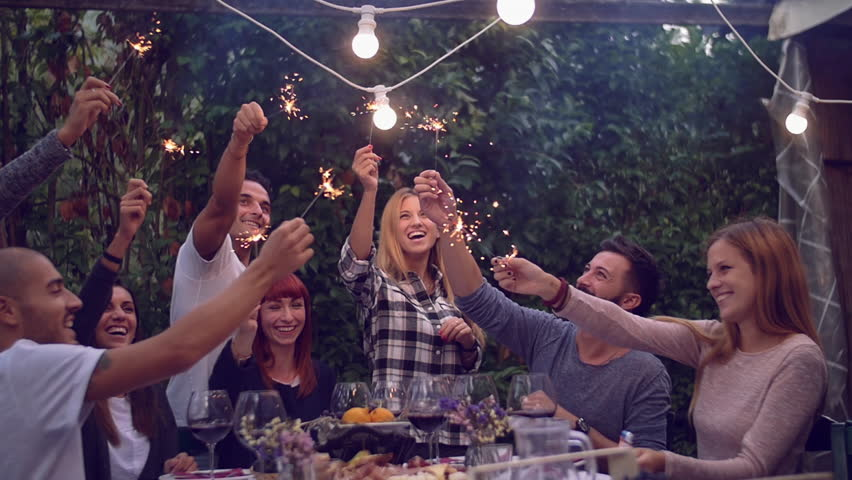 Friends holding lit sparklers at a dinner party  | Shutterstock HD Video #20269078