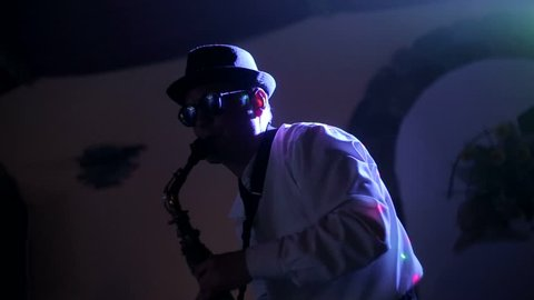 jazz musician playing the saxophone , playing the saxophone ,  music backlit silhouette