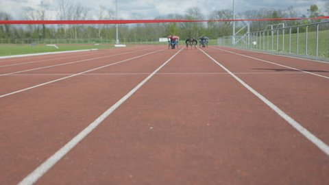 4K Disabled athletes in specialist wheelchairs competing at racing track. Shot on RED Epic.