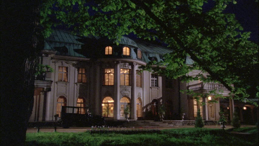 Night left elegant country estate, European chateau mansion, patina roof, French paned windows, arches bottom, balcony, some lights on, period car parked front 1900s