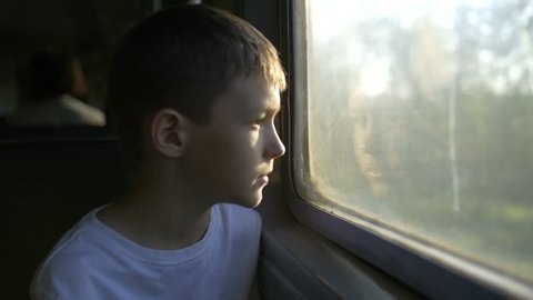 boy looking out train window outside, in the evening, travel