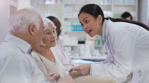 4K Friendly pharmacy worker gives prescription medication to customer in waiting area. Shot on RED Epic.