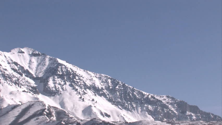 Timpanogos Mountain,Wasatch Range, Rocky Mountains, central Utah. Summit height of 11,749 feet. Pan left. Popular mountain climbing destination. Pan right of bright blue skies and snow covered peaks.