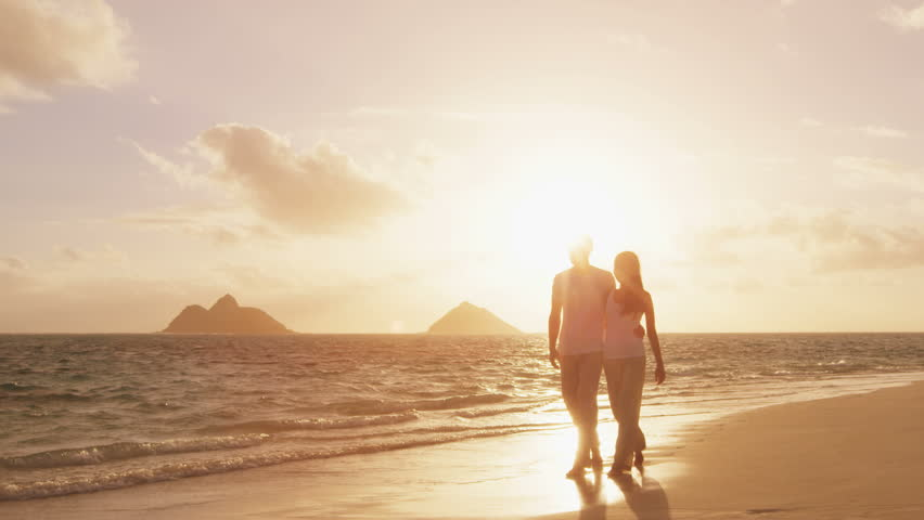 Couple walking at beach at sunset romantic embracing and holding hands. Young couple in love enjoying romance in casual elegant clothing on luxury beach vacation travel holidays, Lanikai, Oahu, Hawaii