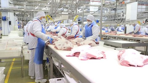 People prepare fresh meat for delivery to stores.