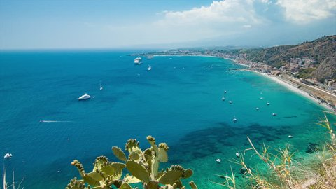 Scenic Taormina Sicily Italy Mediterranean Sea Overlook with Boats and a Cruise Ship in the Clear Blue Water Bay and Green Hillside Flora in the Foreground