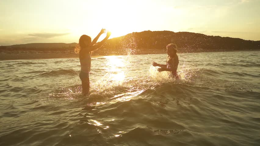 Slow Motion: Two little sisters splash water in the Baltic Sea on one another on the shores of Jurmala, Latvia.