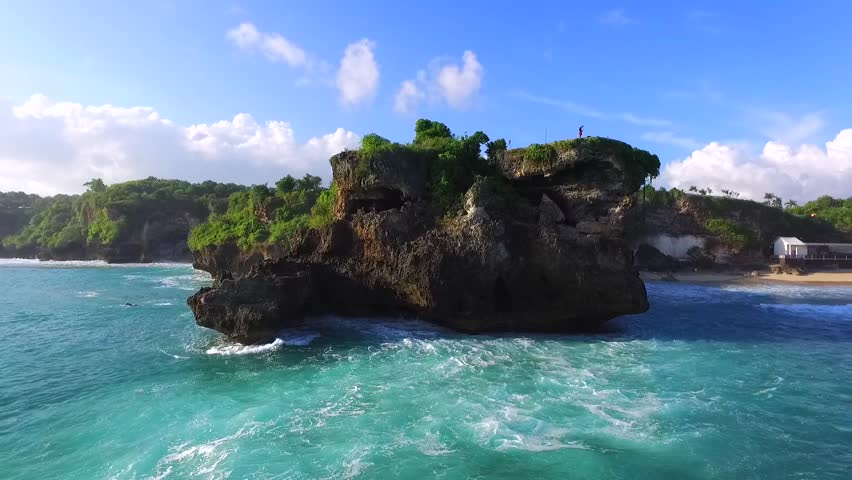 View of the stone cliffs from the ocean side. Balangan beach world famous as a surfer's paradise and a perfect wedding photo location. Aerial view. Ocean surf. Bali Indonesia   Shutterstock HD Video #20480554