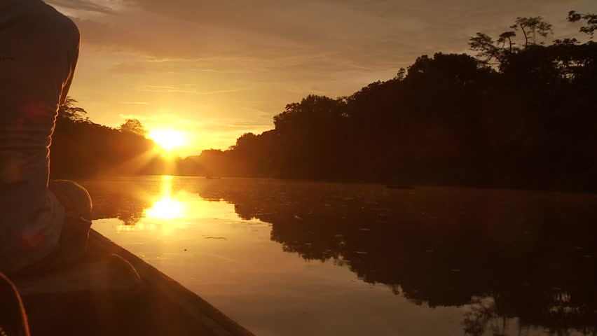 Paddeling With Canoe On The Amazon River in front of the sunset, South America, Peru