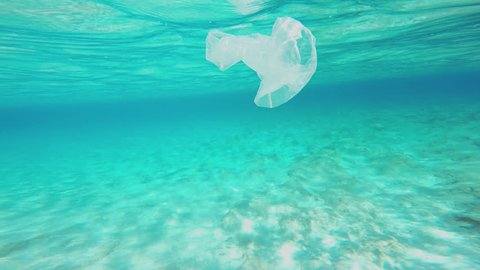 Plastic Pollution Underwater. Camera Is Swimming Around A Plastic Bag Floating Underwater. Tropical, Sunny, Summer, Landscape With A Sun Flooded Sandy Seabed.