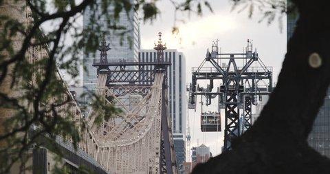 An establishing shot of New York City's Roosevelt Island Tram as it flies alongside New York City's Queensboro Bridge. (Jul 16 - New York City)
