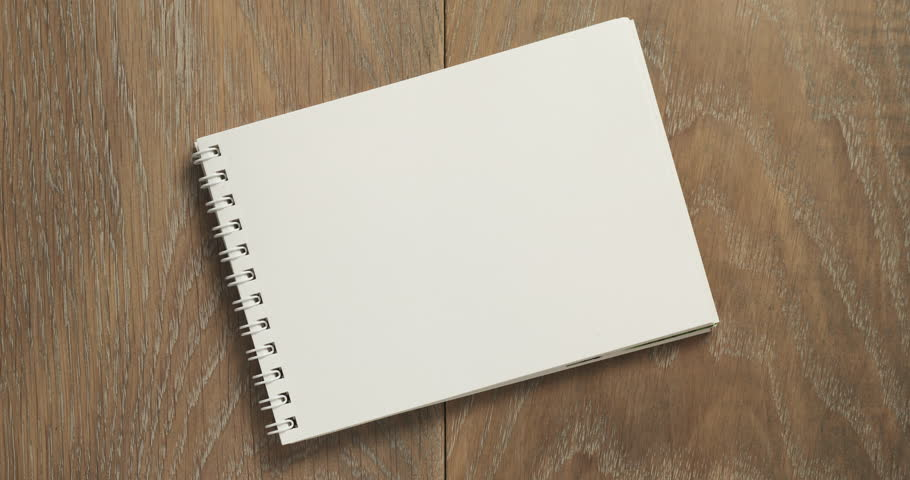 female teen writes new year resolution on blank notepad