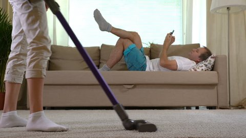 Housewife vacuuming the carpet and her husband lying on the sofa with a smartphone.