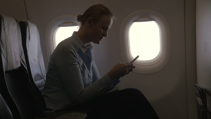 In airplane woman on the window seat making payment with bank card using smartphone and dongle for scanning bank card