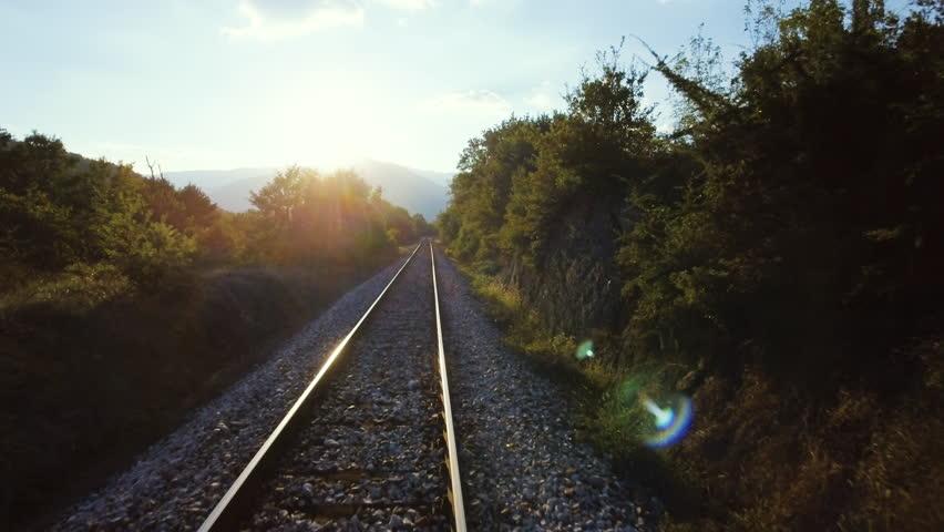 Beautiful countryside scenery railroad aerial drone motion railway train track landscape mountains forest sunshine horizon sun sky