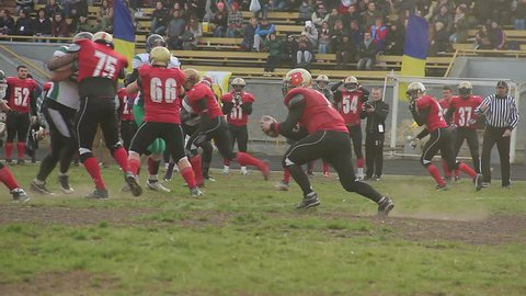KYIV, UKRAINE - OCTOBER 18, 2015: Teams playing American football. Soccer player tackled by strong rivals, sportsman suffers injury during match. Sport teamwork, cooperation, dangerous profession