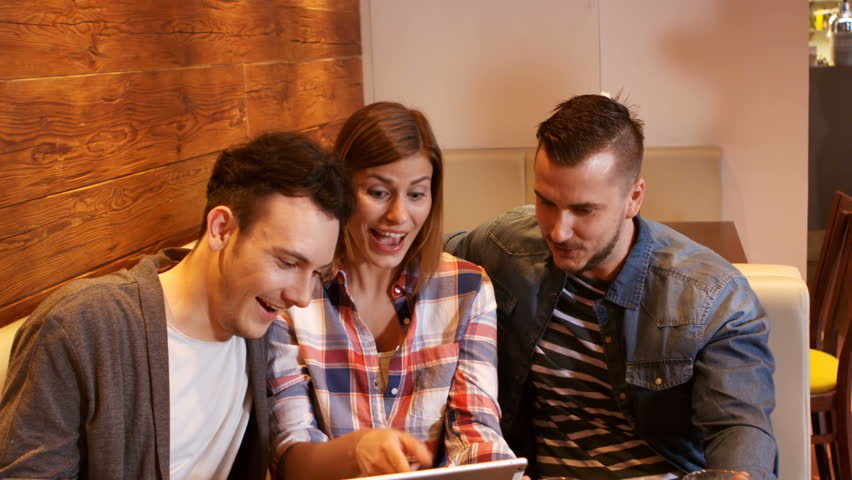 Happy friends using digital tablet while having a glass of beer at restaurant   Shutterstock HD Video #20635054