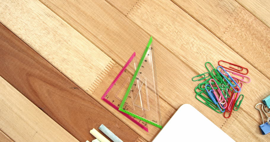 Chalk, set square and paper clip with laptop on a wooden table 4k
