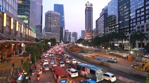 Heavy traffic along Jalan Sudirman at sunset in Jakarta business district in Indonesia capital city. The construction site in the middle is the new MRT project that should ease congestion in the city.