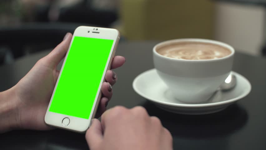 Poland, Lublin - September 27 2016: Girl in the cafe uses a phone with a green screen. In the background is neither black coffee table | Shutterstock HD Video #20663428